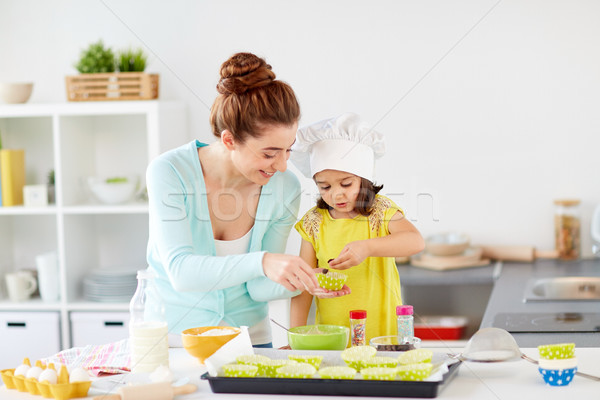 happy mother and daughter baking cupcakes at home Stock photo © dolgachov