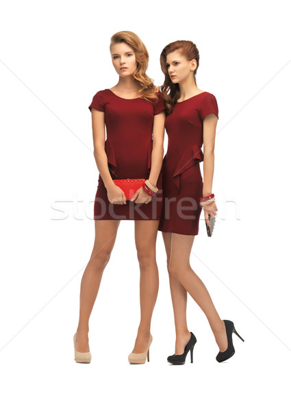 two teenage girls in red dresses with clutches Stock photo © dolgachov