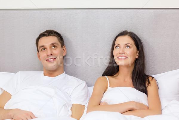 happy couple dreaming in bed Stock photo © dolgachov
