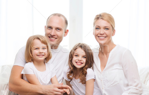 smiling parents and two little girls at home Stock photo © dolgachov