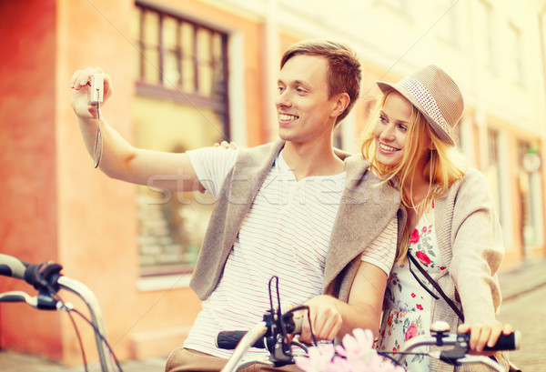 couple with bicycles taking photo with camera Stock photo © dolgachov