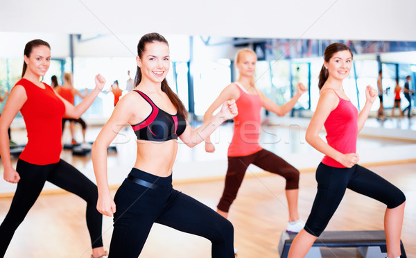 group of smiling people doing aerobics Stock photo © dolgachov