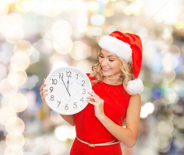 Mosolygó nő mikulás segítő kalap óra karácsony Stock fotó © dolgachov