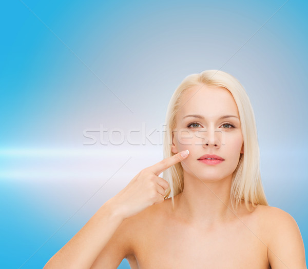calm young woman pointing at her cheek Stock photo © dolgachov