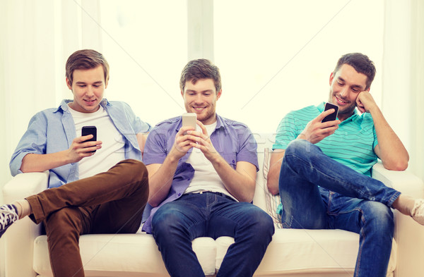 smiling friends with smartphones at home Stock photo © dolgachov