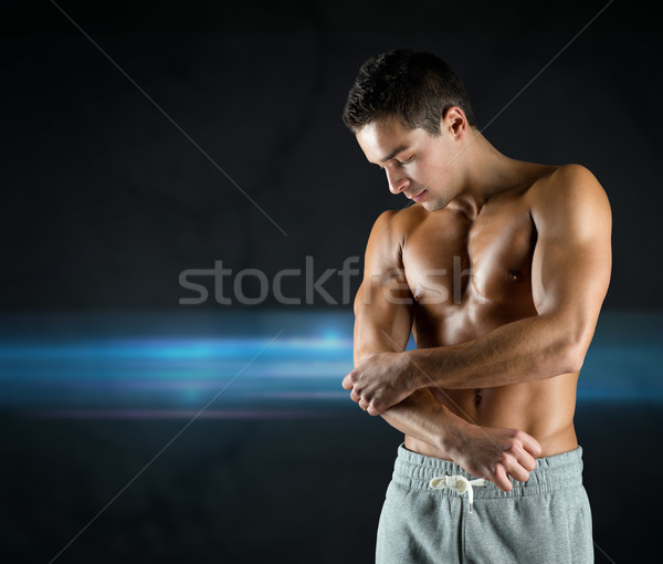 young male bodybuilder injured touching elbow Stock photo © dolgachov