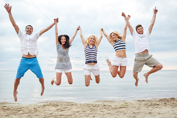 Stock photo: smiling friends in sunglasses walking on beach
