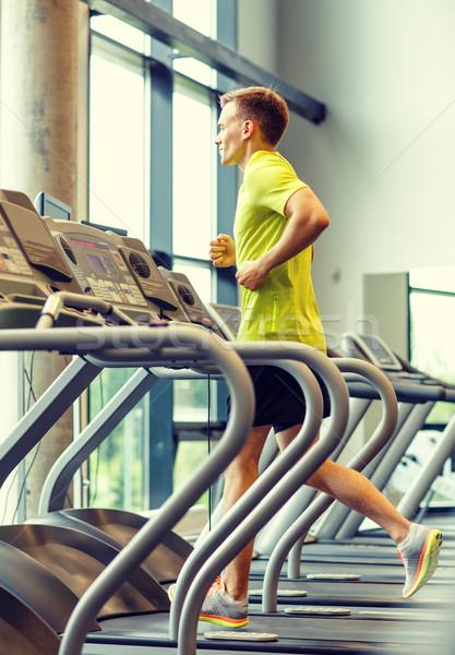 smiling man exercising on treadmill in gym Stock photo © dolgachov
