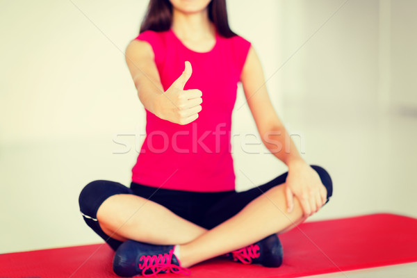 girl sitting in lotus position with thumbs up Stock photo © dolgachov