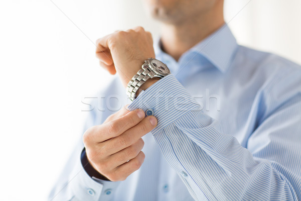 close up of man fastening buttons on shirt sleeve Stock photo © dolgachov