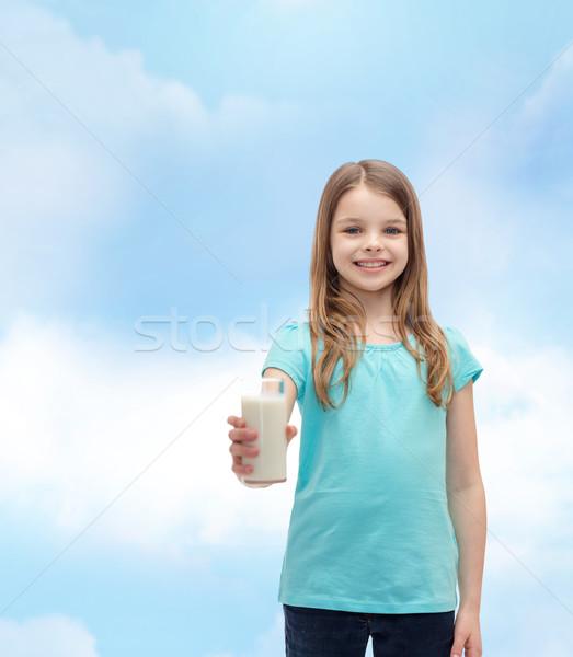 Stock photo: smiling little girl giving glass of milk