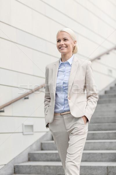 Jovem sorridente empresária caminhada para baixo escada Foto stock © dolgachov