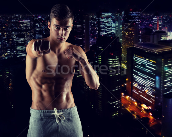 Stock photo: young man in fighting or boxing position
