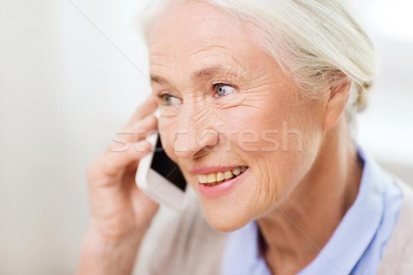 senior woman with smartphone calling at home Stock photo © dolgachov