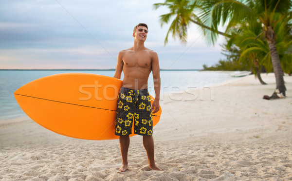 smiling young man with surfboard on summer beach Stock photo © dolgachov