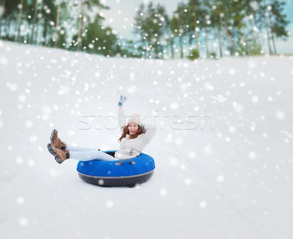 happy teenage girl sliding down on snow tube Stock photo © dolgachov