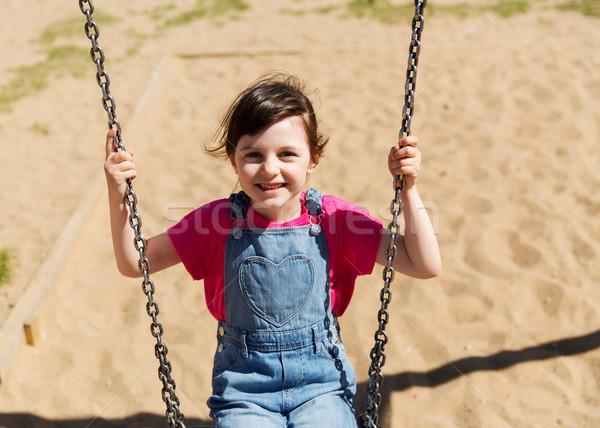 happy little girl swinging on swing at playground Stock photo © dolgachov