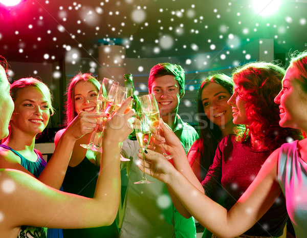 smiling friends with glasses of champagne in club Stock photo © dolgachov