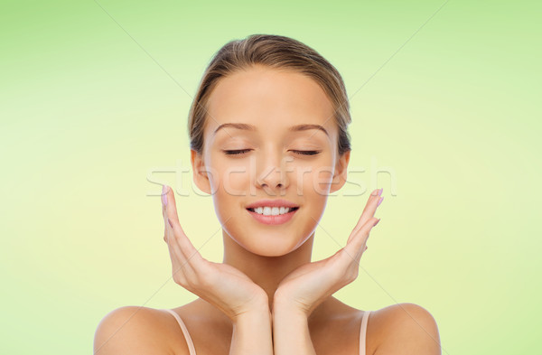 smiling young woman face and hands Stock photo © dolgachov