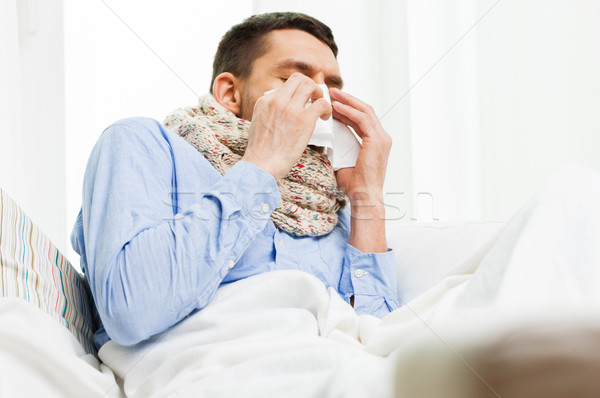 ill man blowing nose with paper napkin at home Stock photo © dolgachov