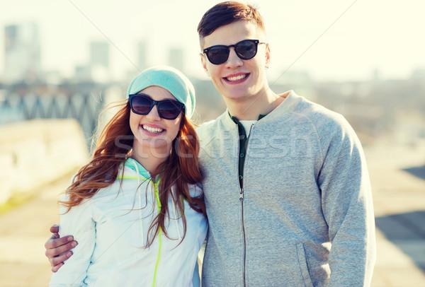 happy teenage couple walking in city Stock photo © dolgachov
