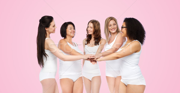 group of happy different women with hands on top Stock photo © dolgachov