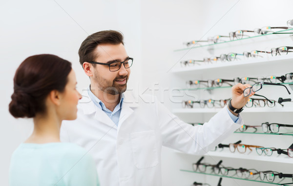 optician with glasses and woman at optics store Stock photo © dolgachov