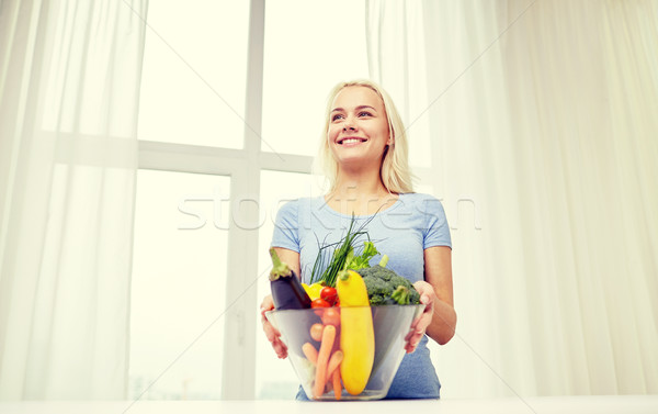 smiling young woman cooking vegetables at home Stock photo © dolgachov