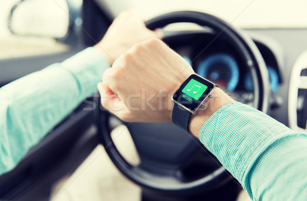 hands with music icon on smartwatch driving car Stock photo © dolgachov