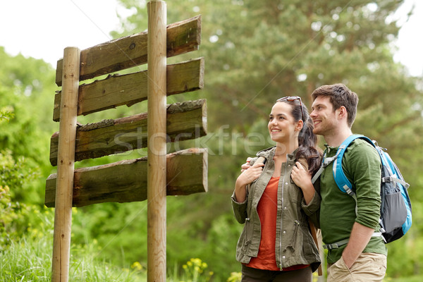 smiling couple at signpost with backpacks hiking Stock photo © dolgachov