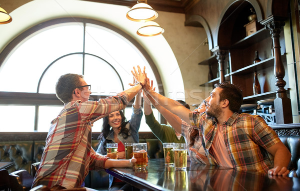 friends with beer making high five at bar or pub Stock photo © dolgachov