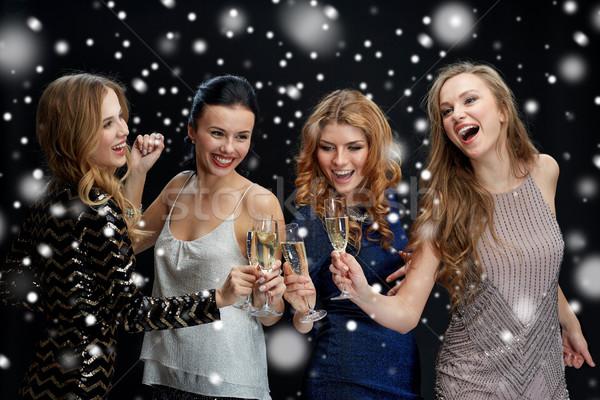 happy women clinking champagne glasses over snow Stock photo © dolgachov