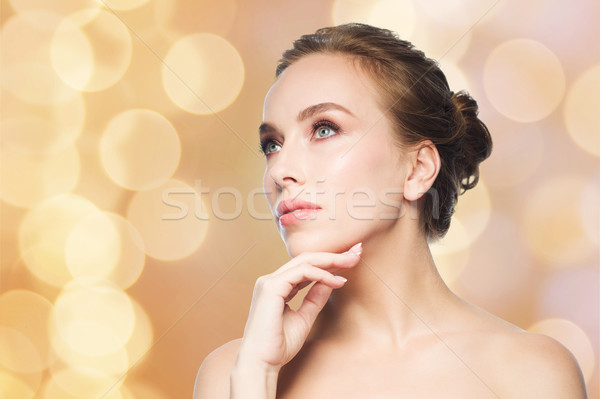 beautiful woman touching her face over lights Stock photo © dolgachov