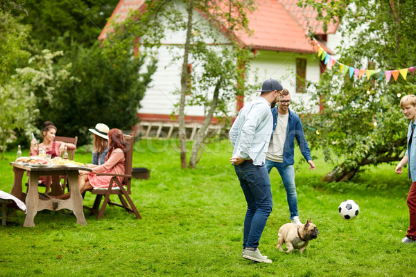 friends playing football with dog at summer garden Stock photo © dolgachov