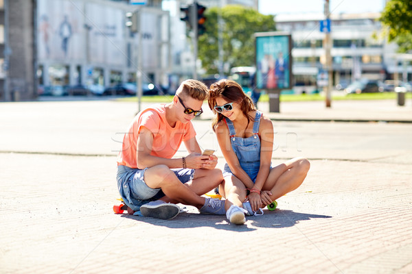 couple with skateboards and smartphone in city Stock photo © dolgachov
