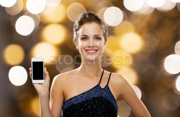 Mosolygó nő estélyi ruha tart okostelefon technológia hirdetés Stock fotó © dolgachov