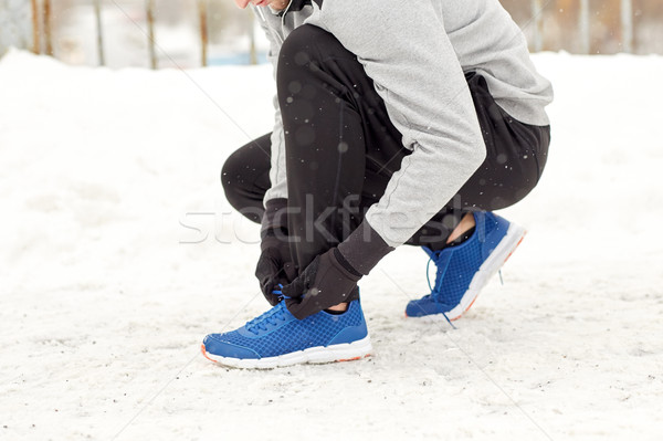 man with earphones tying sports shoes in winter Stock photo © dolgachov