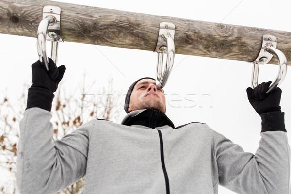 young man exercising on horizontal bar in winter Stock photo © dolgachov