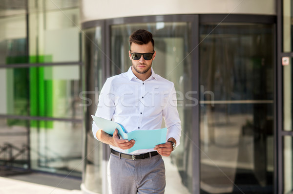 young man with business file on city street Stock photo © dolgachov
