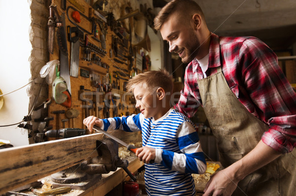 father and son with rasp working at workshop Stock photo © dolgachov