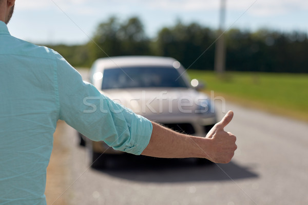 man hitchhiking and stopping car with thumbs up Stock photo © dolgachov