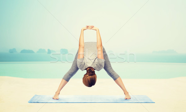 woman making yoga wide-legged forward bend on mat Stock photo © dolgachov