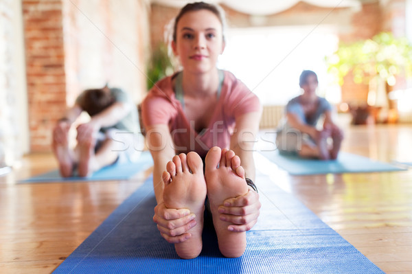group of people doing yoga forward bend at studio Stock photo © dolgachov