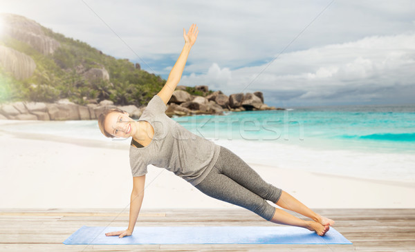 woman doing yoga in side plank pose on beach Stock photo © dolgachov