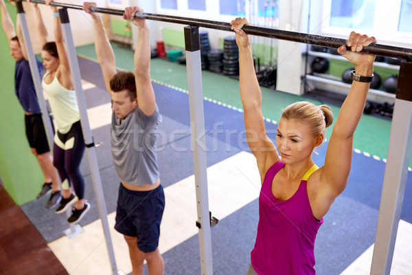 group of people hanging at horizontal bar in gym Stock photo © dolgachov