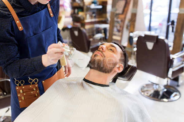 barber cleaning male face with brush at barbershop Stock photo © dolgachov