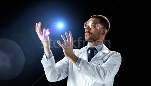 scientist in lab coat and goggles with light Stock photo © dolgachov