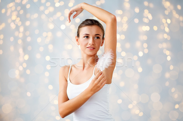 woman with feather touching her armpit at home Stock photo © dolgachov