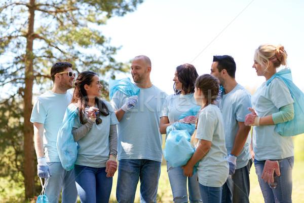 Vrijwilligers vuilnis zakken lopen buitenshuis vrijwilligerswerk Stockfoto © dolgachov