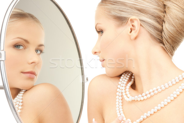 beautiful woman with pearl beads and mirror Stock photo © dolgachov